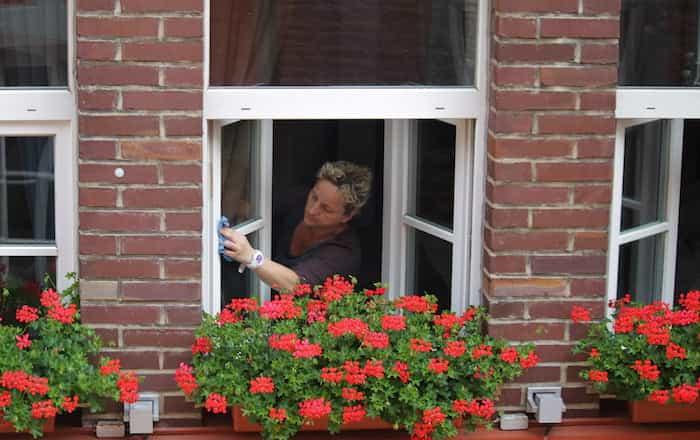 Mujer limpiando la ventana de una casa
