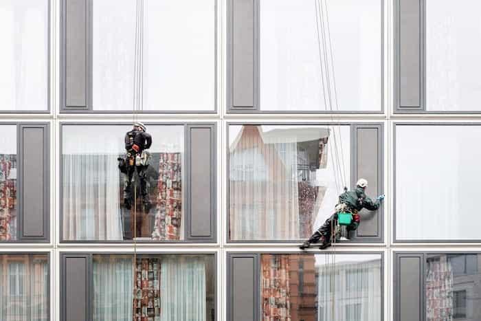 Trabajadores de empresa de limpieza limpiando ventanas a gran altura