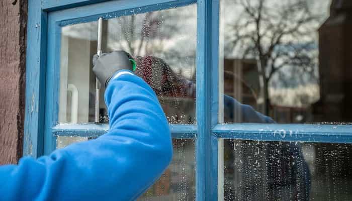 Operario realizando la limpieza de una ventana