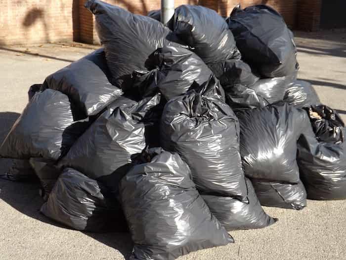 Bolsas de basura con objetos de casa tirados fuera de los contenedores de casa